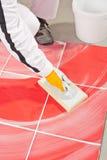 Operaio pulito con la malta liquida dei giunti delle mattonelle del trowel della spugna Fotografie Stock