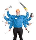 Operaio sorridente con gli strumenti in molte mani Fotografia Stock