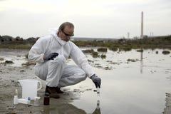 Operaio in un inquinamento d'esame del vestito protettivo fotografie stock libere da diritti