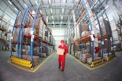 Operaio in uniforme rossa con la casella in magazzino immagine stock libera da diritti