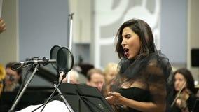 Operasångaren sjunger i mikrofonen med orkesteren stock video