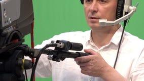 Operatör med en yrkesmässig videokamera i en televisionstudio stock video