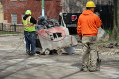 Operate heavy equipment on a Chicago residential. Workers operate heavy equipment on a residential street in Chicago in preparation for sewer pipe replacement Stock Image