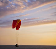 The operated parachute flies low above the sea Stock Photos
