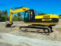 Operating construction equipment, working machinery. Yellow excavator digs the earth Stock Photography