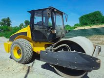 Operating construction equipment, working machinery. A yellow road roller Stock Photo