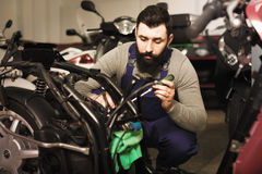 Operating master captures the details on a motorbike. In his workshop Royalty Free Stock Photos