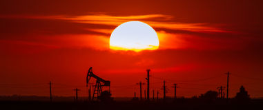 Operating oil and gas well contour, outlined on sunset. Operating oil and gas well contour, outlined on sky with bright solar disc at sunset Royalty Free Stock Photography