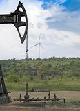 Operating oil. And gas well, profiled on blue sky with clouds and wind turbine stock photography