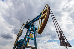 Operating oil and gas well profiled on cloudy sky Stock Image