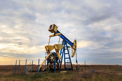 Operating oil and gas well. Oil and gas well profiled on sky, in remote area in Europe Royalty Free Stock Image