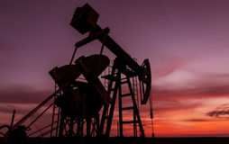 Operating oil and gas well profiled on sunset sky Royalty Free Stock Photo