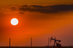 Operating oil and gas well profiled on sunset sky Royalty Free Stock Image