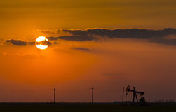 Operating oil and gas well profiled on sunset sky Stock Image