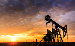 Operating oil and gas well and sunset sky Stock Images