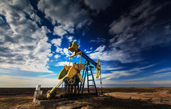 Operating oil well profiled on dramatic cloudy sky royalty free stock photo