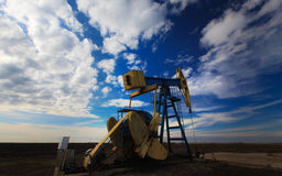 Operating oil well profiled on dramatic cloudy sky Stock Image