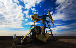 Operating oil well profiled on dramatic cloudy sky Royalty Free Stock Image