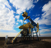 Operating oil well profiled on dramatic cloudy sky Stock Images