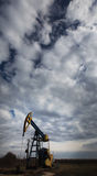 Operating oil well profiled on dramatic cloudy sky Royalty Free Stock Images