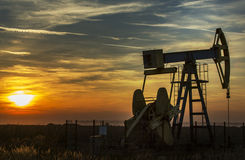 Operating oil well profiled on sunset sky Royalty Free Stock Photography