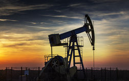 Operating oil well profiled on sunset sky Stock Photos
