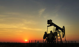 Operating oil well profiled on sunset sky Stock Images