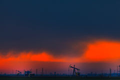 Operating oil wells profiled on dramatic cloudy sky Royalty Free Stock Photography