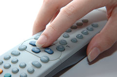 Operating a remote control. Show hand pressing the remote Royalty Free Stock Photo