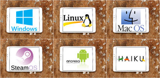 Operating system logos and emblem. Collection of most famous operating system developers logos on white tablet on rusty wooden background Royalty Free Stock Photos
