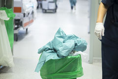 Operating theater surgery trash. Bin and nurse with green plastic bag used to dispose of disposable rubbish after surgical procedure Stock Image