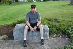 Operation Iraqi Freedom Veteran sitting on a rock. Young Generation X Operation Iraqi Freedom Veteran Royalty Free Stock Images