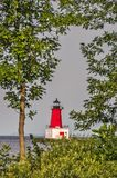 Menominee Pierhead Lighthouse Framed by Trees. Operation of the Menominee Pierhead Lighthouse began in 1877. Focus is on the lighthouse royalty free stock photo