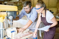 Operation Principle of Drill Press Machine. Concentrated bearded carpenter explaining his attractive apprentice how to use drill press machine, interior of stock photo