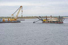 Operation of water equipment. Rope excavator and crane on floating platforms are working on clearing and deepening of the river bed. Volgograd. Volgograd region Stock Photo