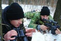 Operations. Soldiers. Command work. Winter. A sniper gun. Snow-covered wood. The field-glass Stock Photo