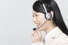 Operator. A young Japanese woman with headset on light gray background Stock Photos