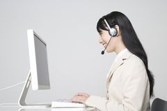 Operator. A Japanese business woman at her desktop with headset Royalty Free Stock Photography