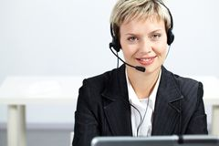 Operator. Portrait of pretty blond operator looking at camera and smiling Royalty Free Stock Photos