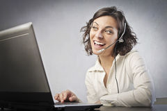 Operator. Smiling female operator talking on the phone and using a laptop Stock Photos