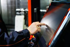 Operator adjusts CNC machine using touch screen royalty free stock photography