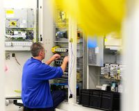 Operator assembles machine in a factory - production of switch c royalty free stock image