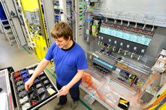Operator assembles machine in a factory - production of switch c royalty free stock photo