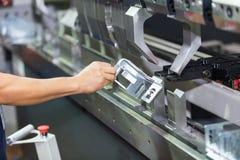 Operator bending metal sheet by sheet bending machine. Cnc control metal sheet bending machine, high precision and high accuracy metal sheet bending machine Royalty Free Stock Image