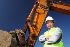 Operator of a excavator. Portrait operator of excavator standing on location site Stock Photos