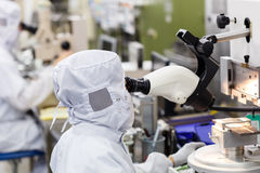 Operator in factory use microscope Stock Photos