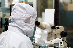 Operator in factory use microscope Stock Image
