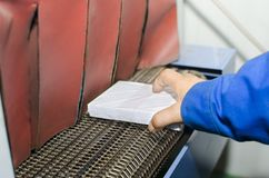 Operator hand place Book on Print plant roller conveyor royalty free stock photo