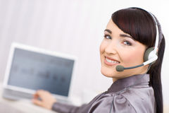Operator with headset. Young female operator wearing a headset works on her laptop, looking at camera royalty free stock image