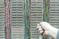 Operator installing telephone switchboard with cables Stock Photo